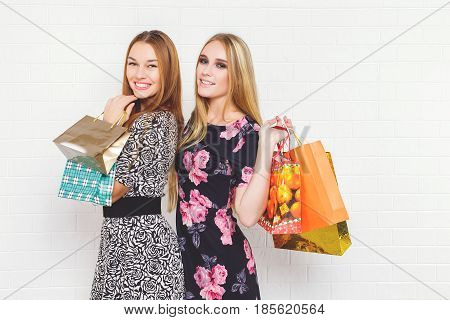 Beautiful teen girls carrying shopping bags, over white background