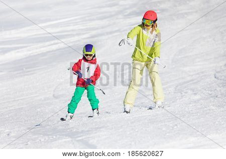 Little boy training skiing with female instructor, holding pole both hands