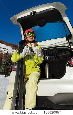 Young woman having rest after skiing, sitting in opened car trunk and drinking warm tea from a cup
