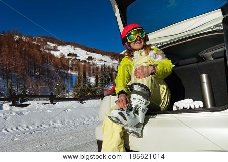 Happy young woman taking off ski boots after skiing, sitting at opened car trunk