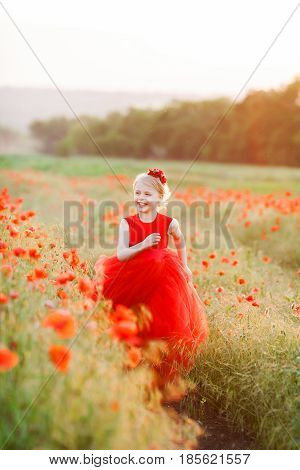 happy childhood, childcare, spring, nature, countryside concept - laughing joyful fair-haired girl with red flower on head in bright red dress running through the field of poppies