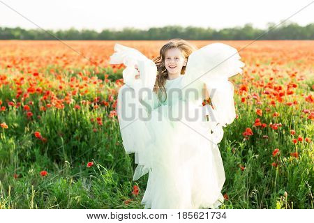 joyful child, holidays, celebration, spring, fashion concept - small excited girl in beautiful turquoise dress with tulle skirt jumping out in field of poppies