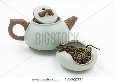 Chinese Oolong Green tea (Tie Guan Yin) in a ceramic bowl with small pot isolated on white.