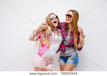 Fashion portrait of two friends posing. modern lifestyle.two stylish sexy hipster girls best friends ready for party.Two young girl friends standing together and having fun.