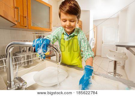 Portrait of happy kid boy rinsing dishes under running water in the sink in the kitchen