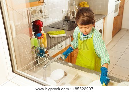 Portrait of six years old boy doing the dishes in the kitchen, view through the window