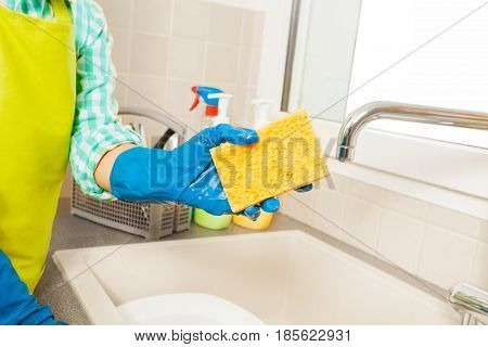 Close-up picture of kid's hand in blue rubber gloves holding yellow sponge against the sink