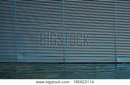 Texture background of metal blinds or portcullis with mirror reflections in the puddles