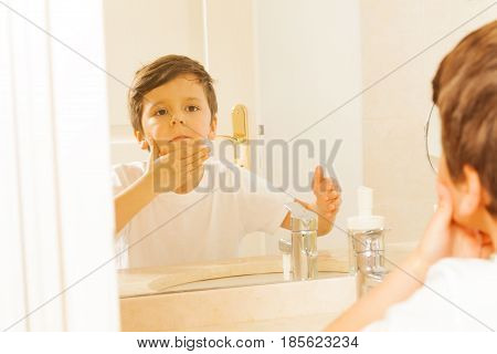 Portrait of six years old boy washing his face and looking in the glass in the bathroom