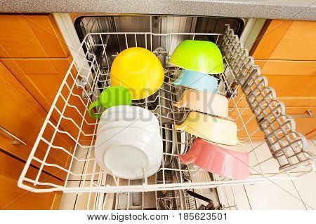 Close-up picture of opened dishwashing machine with clean utensils drying in it's metal dish rack