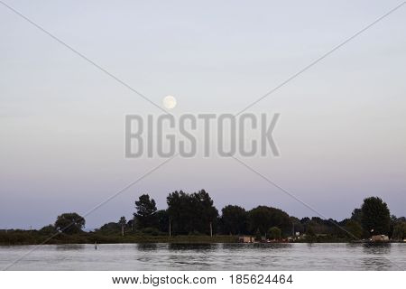 Landscape of the early evening moon over water with small buildings trees and foliage across the river near Cornwall, Ontario in early August.