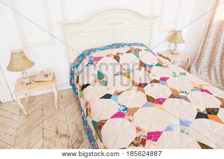 home atmosphere, homecraft, patchwork, quilting, sewing concept - comefort zone in light shades with two bedside table with lamps on them and bed covered in colorful blanket sewed with various patches