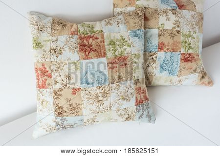 home cosiness, handcraft, sewing, patchwork concept - two decorative cushion made of patches in pastel shades with tender floral prints and image of country house