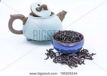 Chinese Oolong Dark Red tea (WuYi Rou gui) in a blue ceramic bowl in a blue ceramic bowl with small clay pot isolated on white.