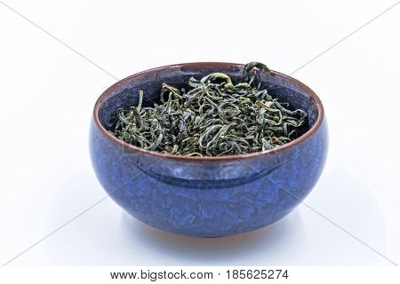 Chinese Green tea. (Huang Shan Mao Feng) in a blue ceramic bowl isolated on white.