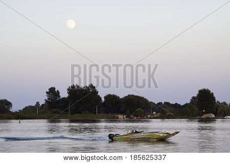 Cornwall, Ontario - August 9, 2014 -- Close up of the early evening moon over water with a speed boat racing by and a cargo ship going through a canal edged by trees and foliage near Cornwall Ontario in early August.