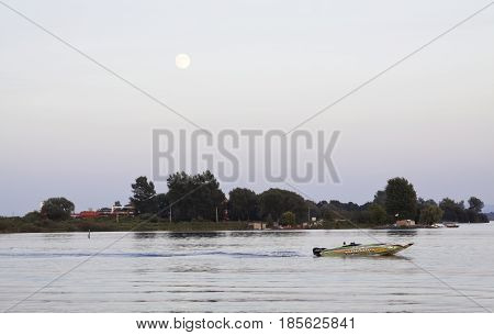 Cornwall, Ontario - August 9, 2014 -- Close up of the early evening moon over water with a speed boat racing by and a cargo ship going through a canal edged by trees and foliage near Cornwall, Ontario in early August.