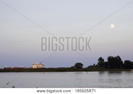 Cornwall, Ontario - August 9, 2014 -- Landscape of the early evening moon over water with a cargo ship going through a canal edged by trees and foliage as ducks swim in the river near Cornwall, Ontario in early August.