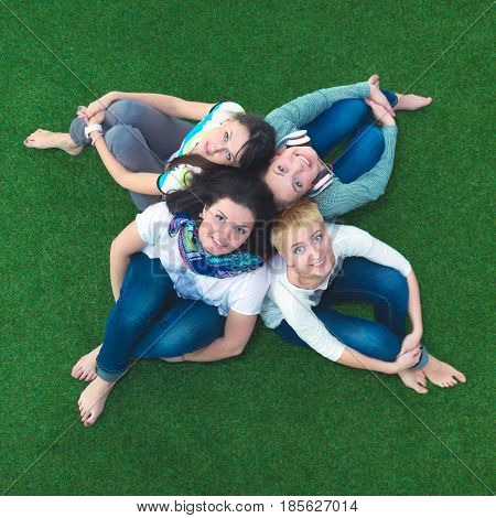 group of smiling friends lying on grass in circle. Relax