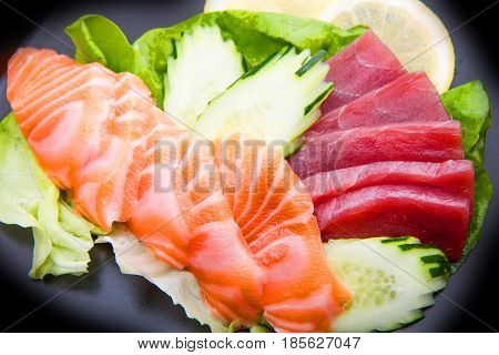 tuna and salmon sashimi on black dish