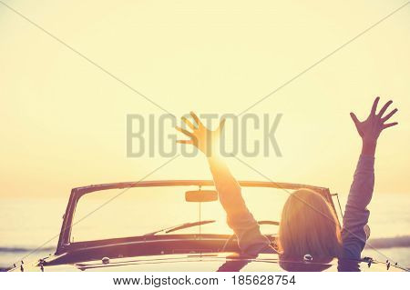 Woman driving a convertible car at the beach. The car is a vintage model shot at sunset or sunrise. The woman looks happy and could be on vacation or having an adventure. She has her arms raised in celebration. Rear view defocussed with copy space