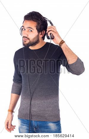 Happy handsome beard young man listening to music and trying to listen to someone guy wearing gray t-shirt and jeans with headphones isolated on white background
