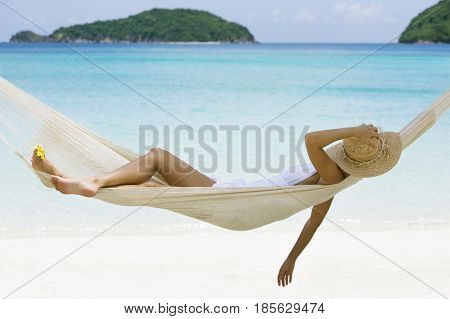 woman relaxing in a hammock on tropical beach