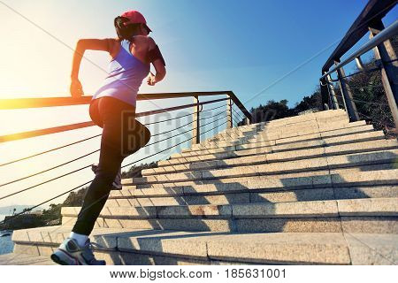 Sportswoman running up on stone stairs doing running exrecise