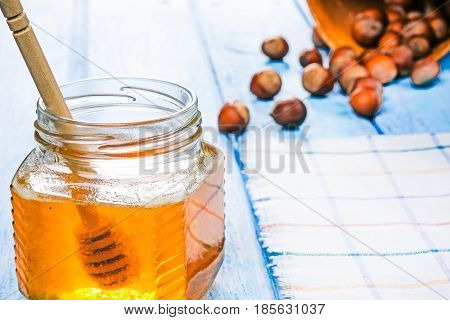 Hazelnuts in shell scattered on blue plank table. Honey jar with dipper next to the nuts