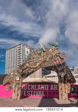 Auckland New Zealand - March 4 2017: Wooden colorful festive gate at Auckland Art Festival on Aotea Square under blue sky with white clouds. Combination of Maori symbols masks and art objects.