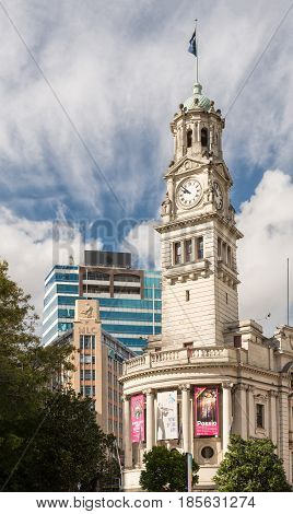 Auckland New Zealand - March 4 2017: The white stone Clock Tower of town hall with theater posters and flag. Green vegetation and blue sky with white clouds.