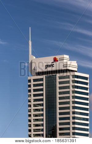 Auckland New Zealand - March 4 2017: White stone and black window office building of PricewaterhouseCoopers the auditing company isolated against blue sky.