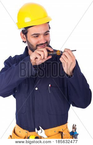 Handsome beard young worker smiling and using a screwdriver guy wearing workwear and yellow helmet with belt equipment isolated on white background