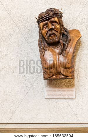 Auckland New Zealand - March 4 2017: The Tear brown wooden sculpture hangs in Holy Trinity Cathedral celebrating organ transplant donors and recipients. White beig wall. Face of crying Christ with thorn crown.