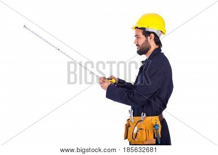 Handsome beard young worker looking side and holding a measure guy wearing workwear and yellow helmet with belt equipment isolated on white background