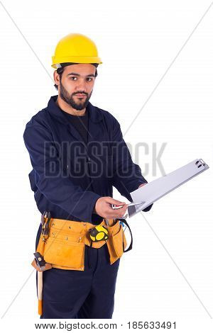 Handsome beard young worker holding a clipboard and showing to it by the pen guy wearing workwear and yellow helmet with belt equipment isolated on white background