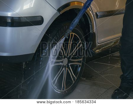 The worker washes the wheel of a car close up