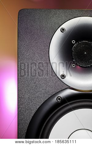 DJ studio monitor speaker with disco lighting background. Nightclub party sound system equipment.