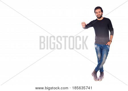 full length shot of a happy beard young man smiling with hand in pocket and rising the other hand guy wearing gray t-shirt and jeans isolated on white background