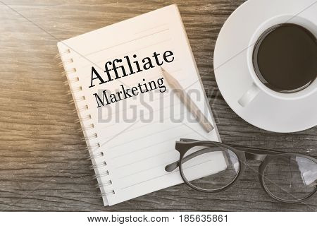 Concept Affiliate Marketing message on notebook with glasses pencil and coffee cup on wooden table.