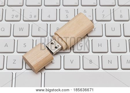 USB flash drive wooden on white keyboard