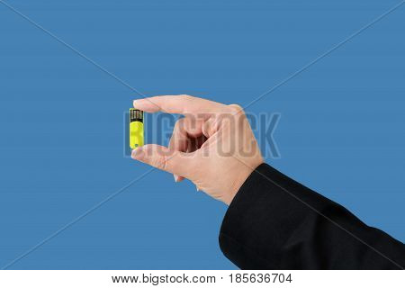 Yellow flash drive on hand with isolated blue background
