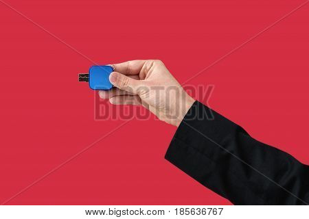 Blue flash memory on hand with isolated red background