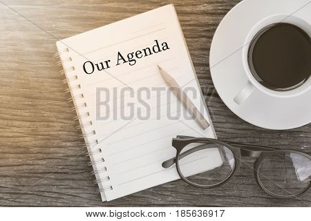 Concept Our Agenda message on notebook with glasses pencil and coffee cup on wooden table.