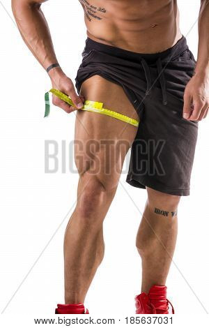 Muscular bodybuilder man measuring thigh with tape measure, close-up isolated on white background. Unrecognizable person