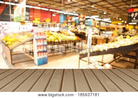 Empty wooden table over blurred shopping mall background for product display montage.