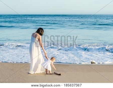 Mother and her baby girl on the sandy beach near ocean in sunny day/curiosity concept