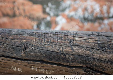 Graffiti on Worn Log Hand Rail shows vandalism in parks