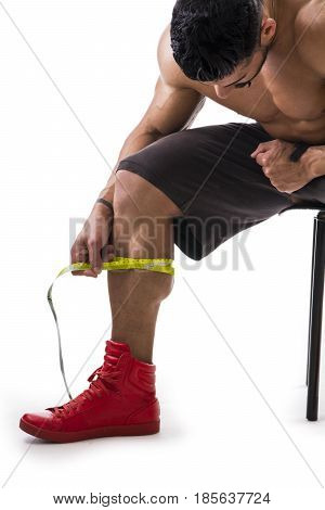Muscular bodybuilder man measuring calf with tape measure, close-up isolated on white background. Unrecognizable person