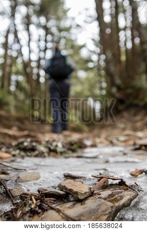 Hiker on Icy Trail with focus on foreground